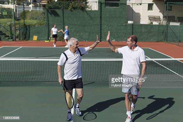 older men high-fiving on tennis court - doubles stock photos and pictures
