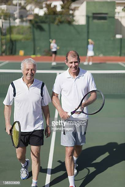older men walking on tennis court - doubles stock photos and pictures