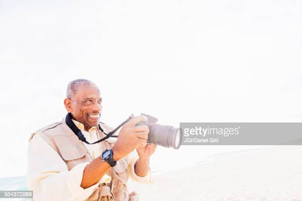 Older mixed race man photographing on beach