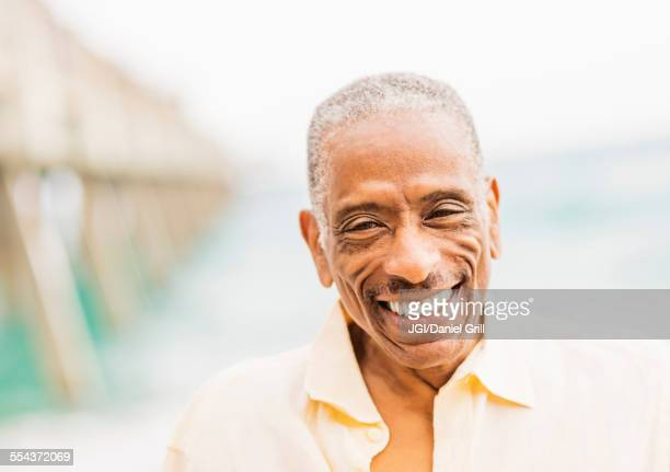 Older mixed race man smiling on beach