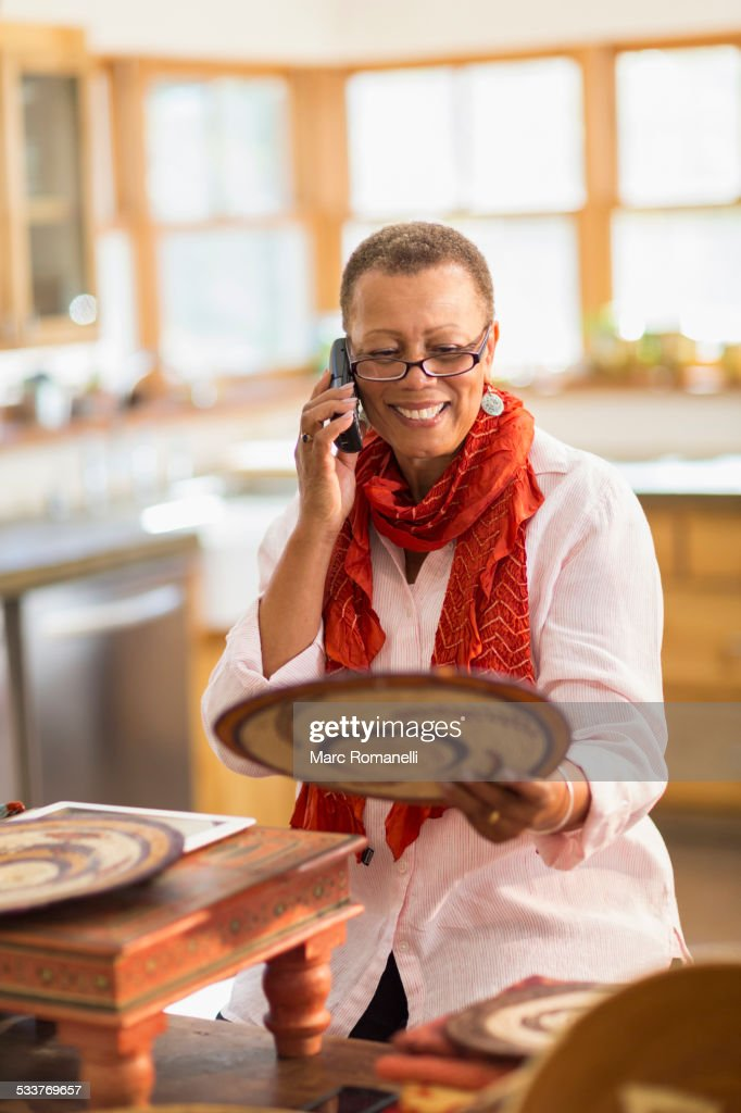 Older mixed race woman talking on telephone in home office : Foto stock