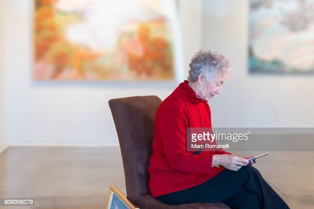 Older mixed race woman using digital tablet in art gallery