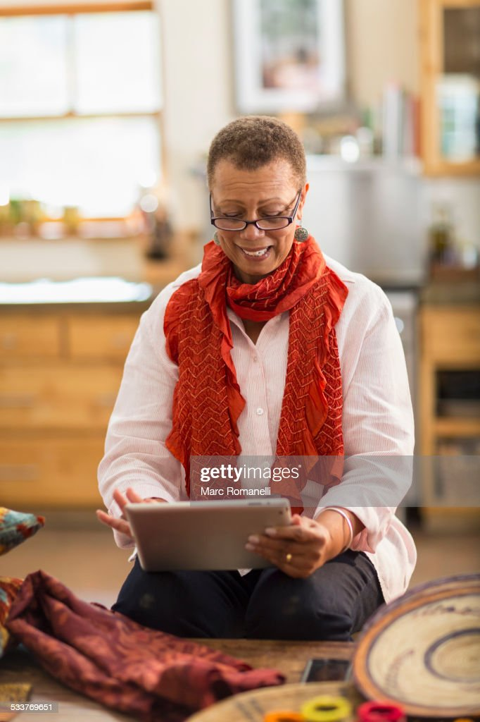 Older mixed race woman using digital tablet in home office : Foto stock