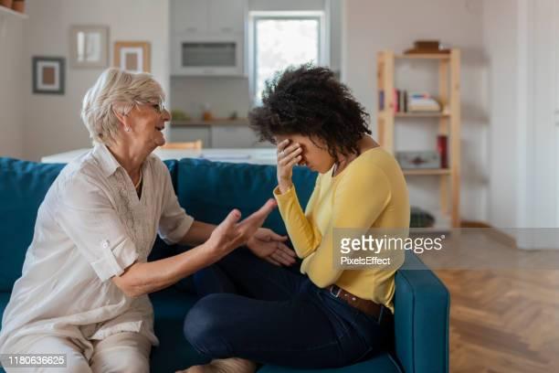 oudere moeder trooting sad volwassen aangenomen gemengde ras gegroeid dochter - gemengde afkomst stockfoto's en -beelden