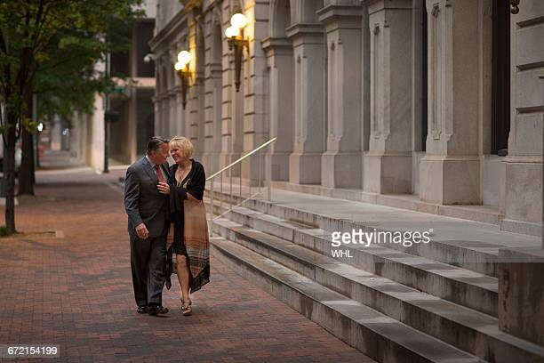 older romantic couple walking on city sidewalk - dämmerung stock-fotos und bilder