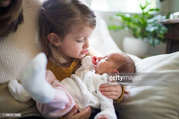 older sister holding newborn baby girl - yawning mother child stock photos and pictures