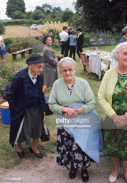 Older village residents wearing their Sunday best clothes socialising at the church fete in the Rectory garden at Pembridge in England circa June...