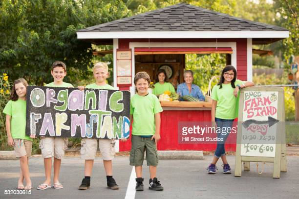 Older woman and children at organic farm stand