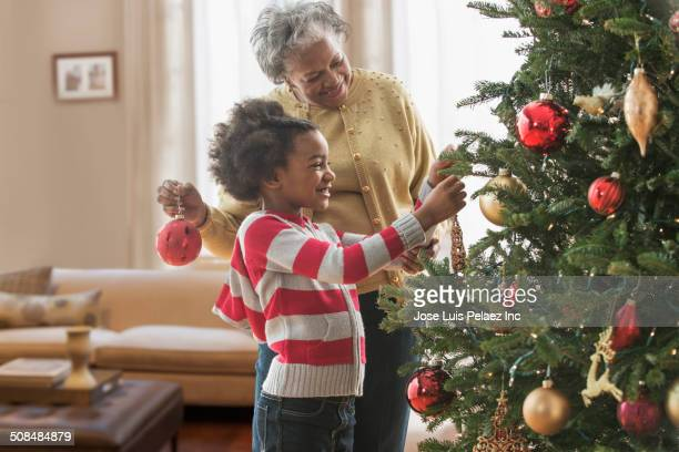 Older woman and granddaughter decorating Christmas tree