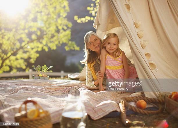 Femmes âgées et petite-fille assis sous une tente