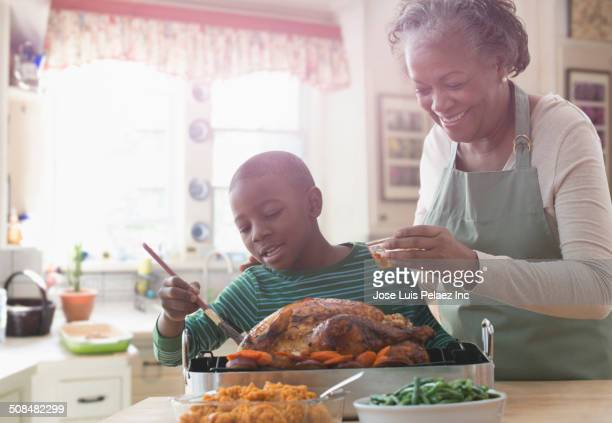 Older woman and grandson cooking together in kitchen