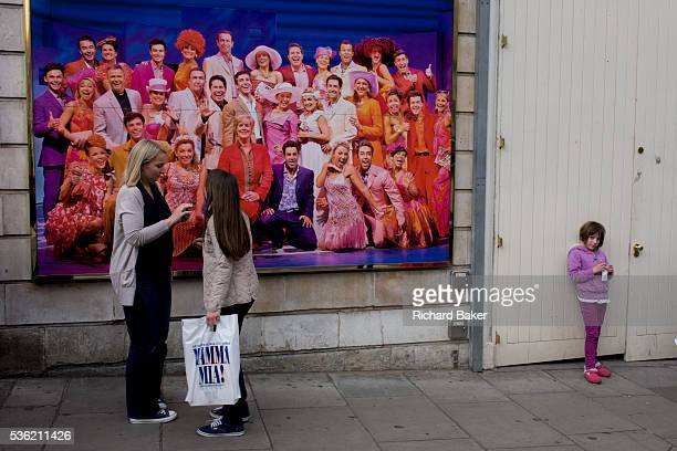 Older woman and younger girls in front of poster for Mamma Mia musical in London's West End. Wearing a similar purple to the show's poster, a young...