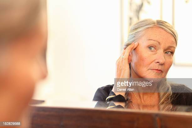 Older woman applying makeup in mirror