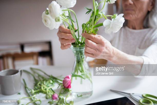 Older woman arranging flowers