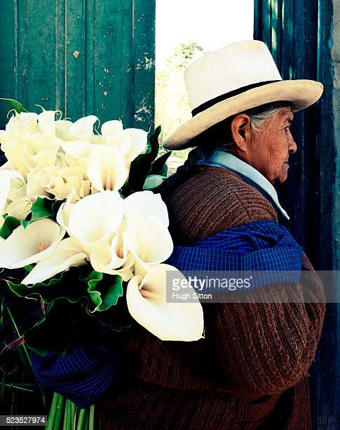 older woman carrying lilies. ollantaytambo. cusco. peru. - hugh sitton stock pictures, royalty-free photos & images