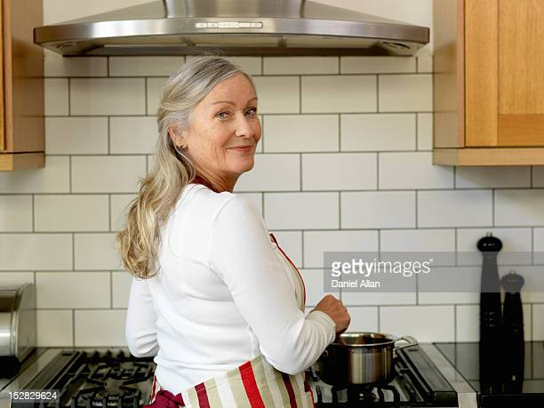 older woman cooking in kitchen - looking over shoulder stock pictures, royalty-free photos & images