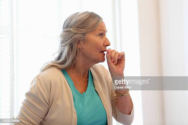 older woman coughing into her hand - cough stock pictures, royalty-free photos & images