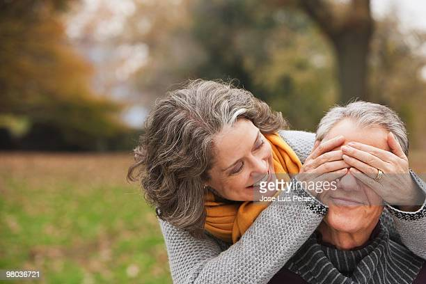 Older woman covering husband's eyes