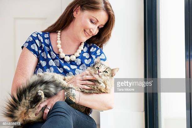 older woman cuddling cat