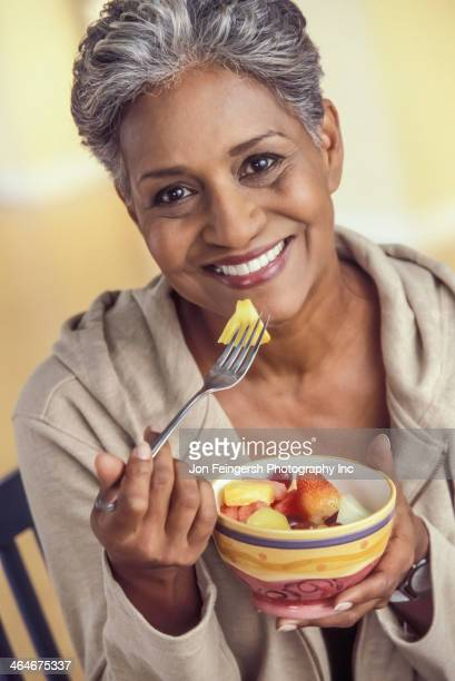 Older woman eating bowl of fruit