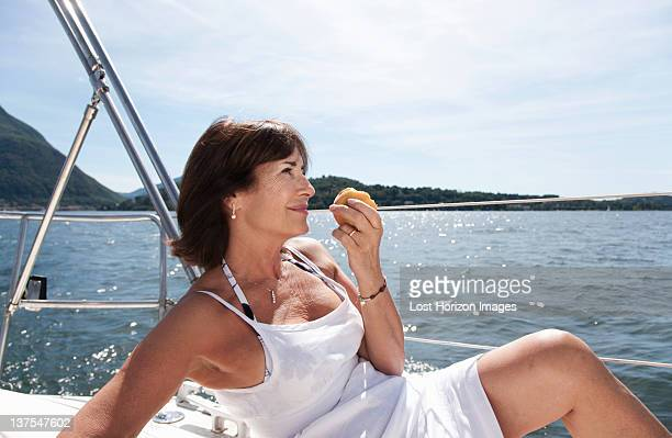 Older woman eating on sailboat
