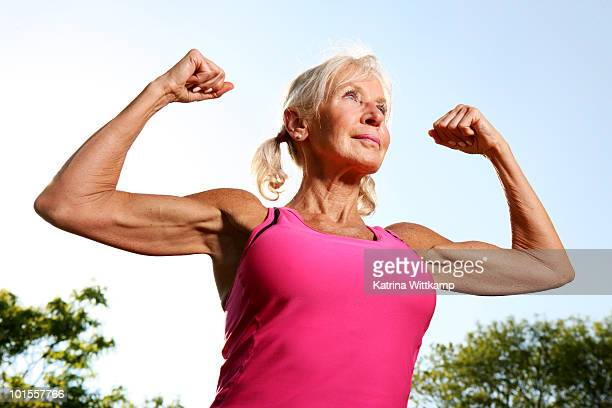 Older woman flexes muscles.
