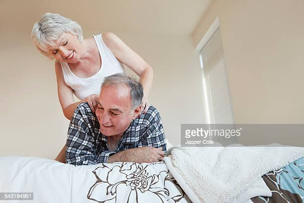 older woman giving husband back massage on bed - massage homme femme photos et images de collection