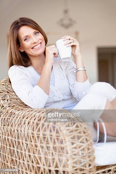 Older woman having coffee in armchair