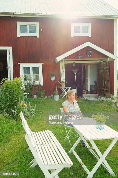Older woman having coffee in backyard