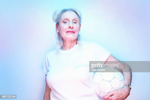 older woman holding football - tee sports equipment stock photos and pictures
