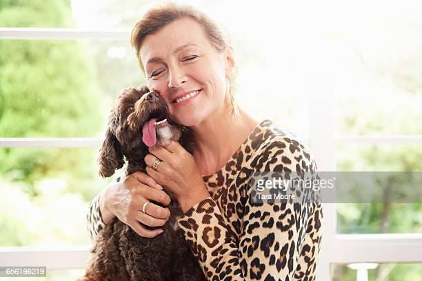 older woman hugging dog
