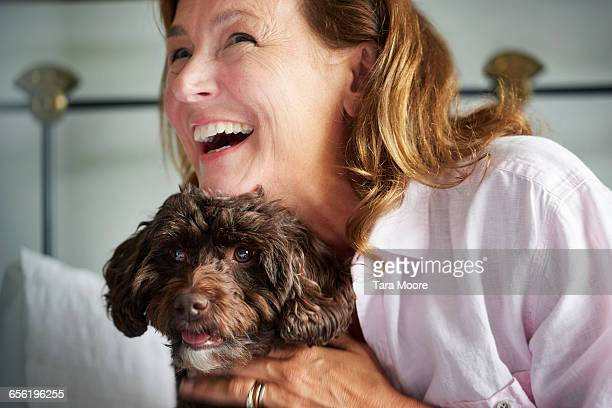 older woman hugging dog - roze bloes stockfoto's en -beelden