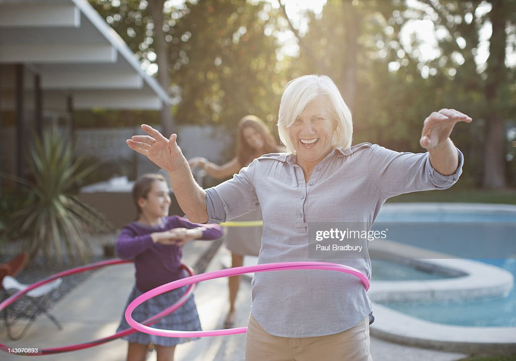 Older woman hula hooping in backyard : Stock Photo