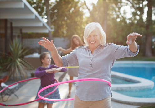 Older woman hula hooping in backyard - gettyimageskorea