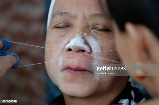 older Woman in bangkok gets facial hair removal runt eyebrows threading procedure