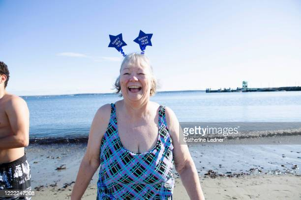 Older woman in bathing suit laughing and wearing a headband with stars