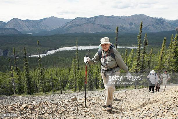 older woman leading group of hikers - hiking pole stock pictures, royalty-free photos & images