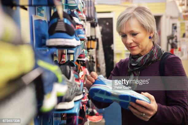 older woman looking at running shoes in shop - shoe store stock pictures, royalty-free photos & images