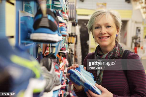Older woman looking at running shoes in shop