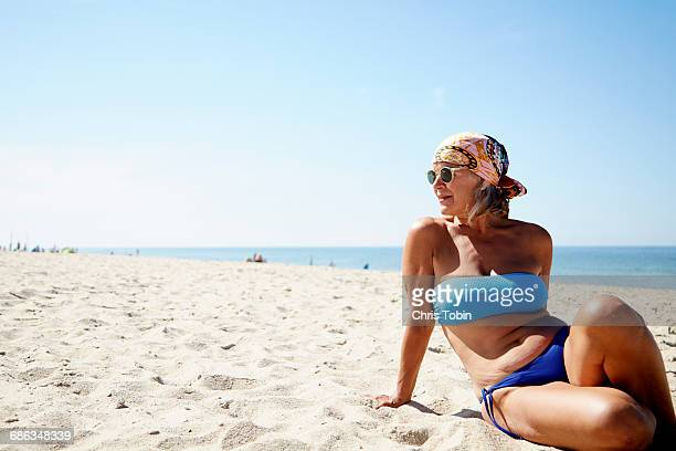 older woman lounging on the beach - old woman in swimsuit stock pictures, royalty-free photos & images