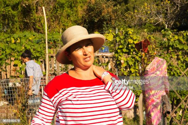 older woman massaging shoulder muscles in a garden setting garden wearing hat and brightly clothed, sydney, australia - scarecrow faces stock photos and pictures