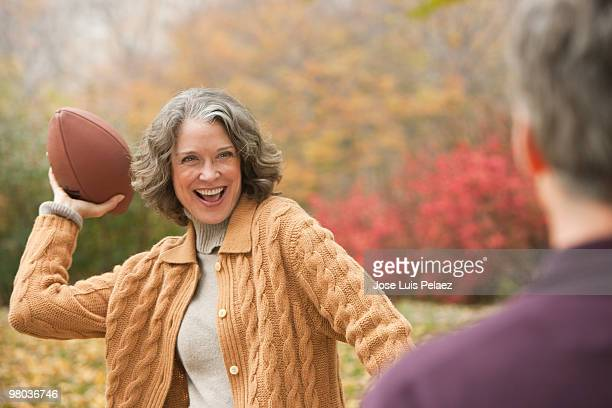 Older woman playing football with husband