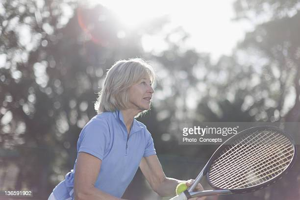 Older woman playing tennis outdoors