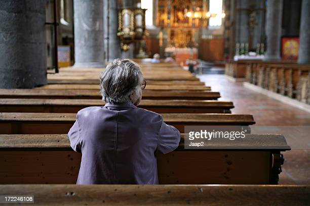 older woman praying in an almost empty church, rear view - church stock pictures, royalty-free photos & images