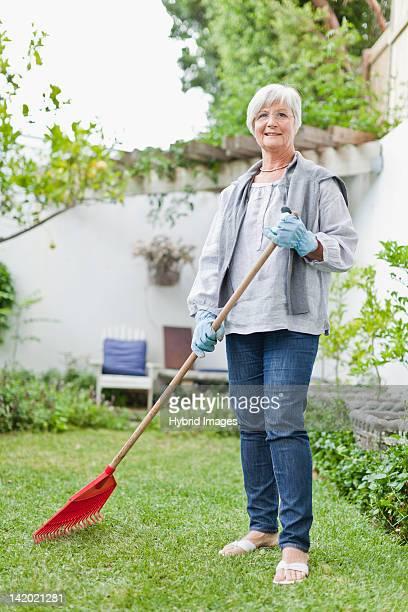 older woman raking in backyard - rake stock pictures, royalty-free photos & images