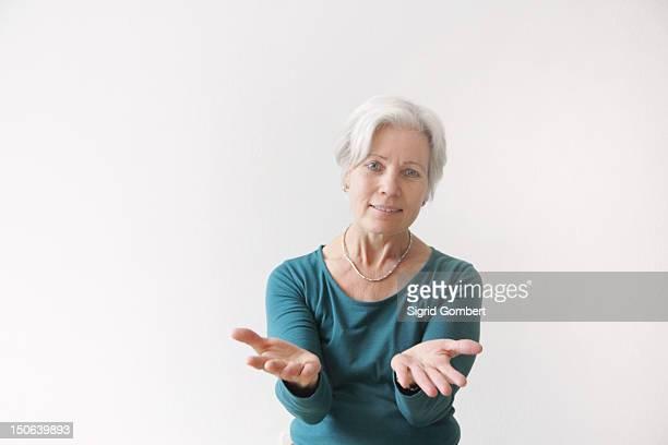 older woman reaching forward - sigrid gombert fotografías e imágenes de stock