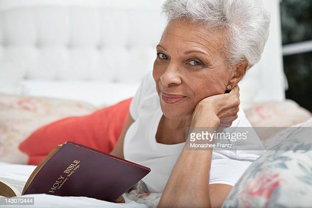 Older woman reading Bible in bed