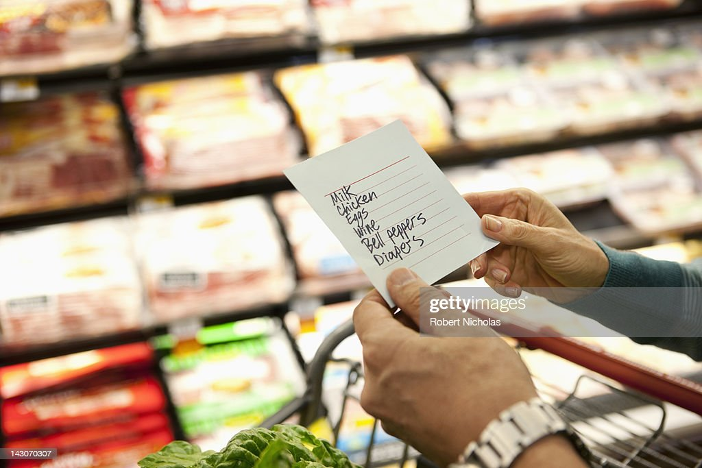 Older woman reading grocery list in supermarket : Stock Photo