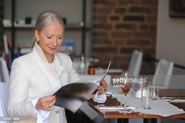 ältere frau lesen magazin im café - food journal stock-fotos und bilder