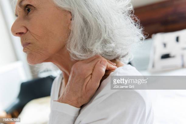 Older woman rubbing the neck